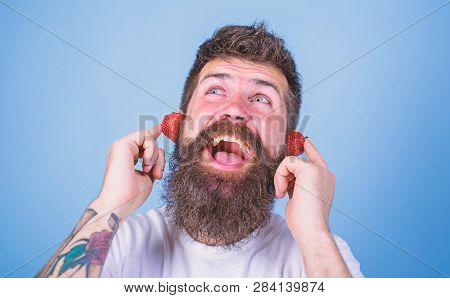 Summer Hit Concept. Man Bearded Hipster Red Ripe Strawberry Ears As Headphones. Guy Enjoy Juicy Soun