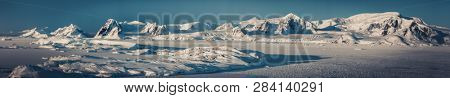 Panorama view of Antarctica nature, sunlit snow covered Penola bay. Stunning aerial shot. The ice surface of the South Pole. Picturesque snow covered mountains next to the frozen Antarctic shoreline