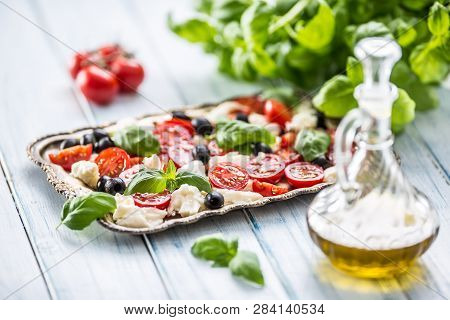 Caprese Salad With Mozzarella Cheese Ripe Tomatoes Olives And Basil Leaves. Italian Or Mediterranean