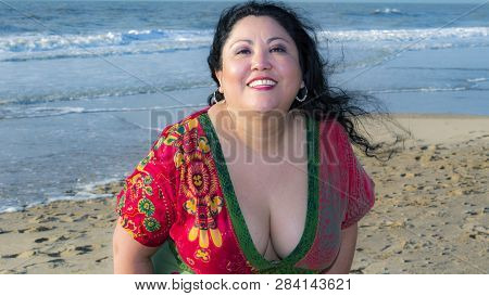 Sexy mature latin Mexican woman with long black hair wearing a open sexy colorful dress with very deep neckline standing on a beach with sea in the background looking and smiling into the camera her hair moving in the wind. poster