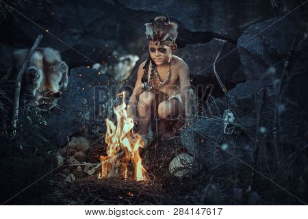 Caveman, Manly Boy At The Fire. Scary Young Primitive Boy Outdoors Near Bonfire. Witch Craft Concept