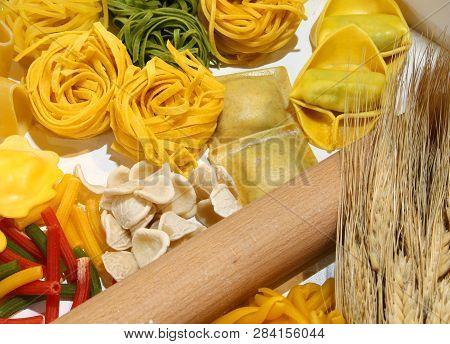 Italian Homemade Pasta With Various Sizes Called Tortellini Ravioli Tagliatelle And Ripe Wheat Spike
