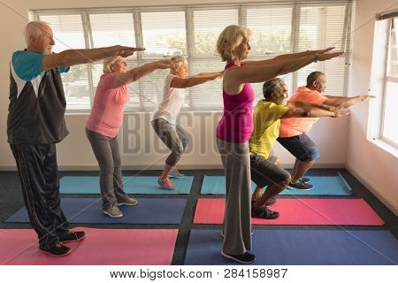 Side view of group of active senior people performing exercise on yoga mat at home
