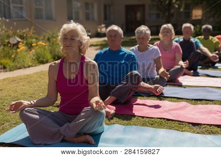 Front view of group of active senior people performing yoga in the park. They are sitting on yoga mat