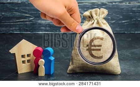 A Money Bag With A Euro Sign And A Family Standing Near The House. The Concept Of Home Buying. House