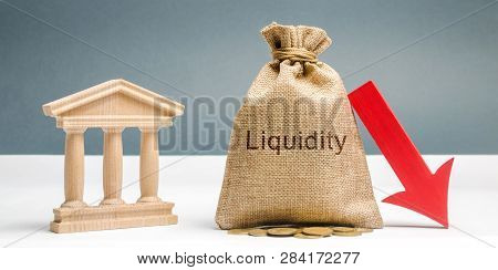 Money Bag With The Word Liquidity, Down Arrow And Bank Building. The Concept Of Market Decline. Drop