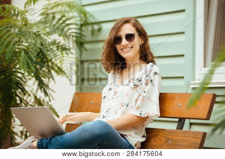 Side View Of Ypung Woman In Sunglasses Sitting On Bench In Park And Using Laptop Computer