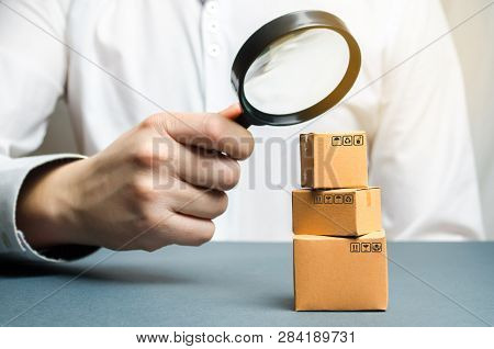 A Man Holds A Magnifying Glass Above The Boxes. Examination Of Goods For The Presence Of Contraband,
