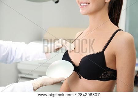 Doctor Showing Silicone Implant For Breast Augmentation To Patient In Clinic, Closeup. Cosmetic Surg