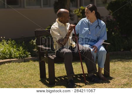 Front view of young smiling female doctor talking with happy senior man hands leaning on a cane while sitting on bench on sunny day in garden