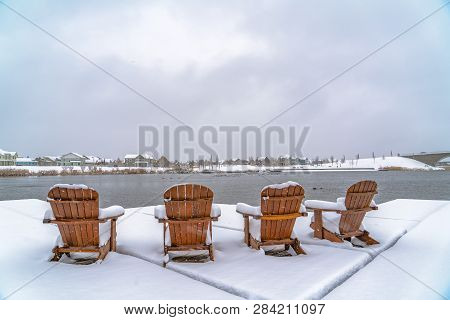 Wooden Chairs On Deck Overlooking Lake And Homes