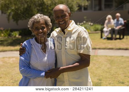Front view of happy senior couple holding hands and looking at camera in garden