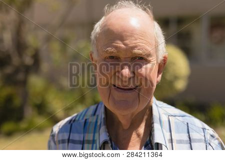 Close- up of happy senior man looking at camera on sunny day in garden