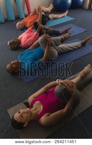 High angle view of young female trainer exercising with senior people in fitness studio
