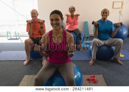 Front view of senior people exercising with female trainer using dumbbells in fitness studio