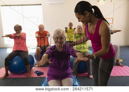 Front view of happy Young female trainer assisting senior woman to do exercice ball in fitness studio