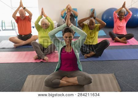 Front view of senior people doing yoga with female trainer in fitness studio