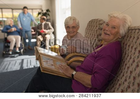 Side view of happy and smiling senior women with photo album looking at camera in home