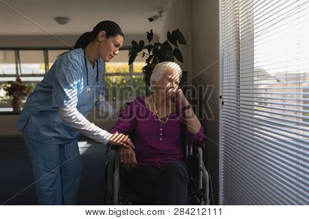Front view of female doctor consoling sad disable senior woman at nursing home