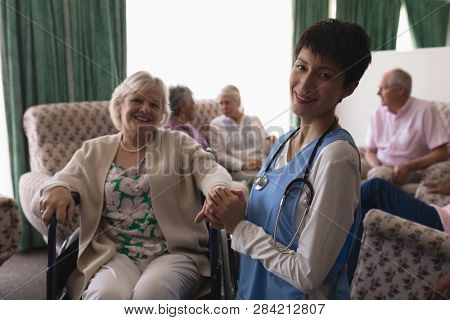 Front view of female doctor holding hands of disabled smilling senior woman in living room while senior people sitting behind on sofa at home