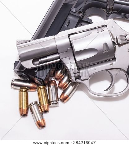 A 357 Magnum Revolver On Top Of A 40 Caliber Pistol With Eight 40 Caliber Hollow Point Bullets On A