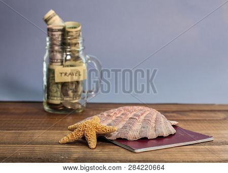 Saving money for travel in jar with shell and starfish