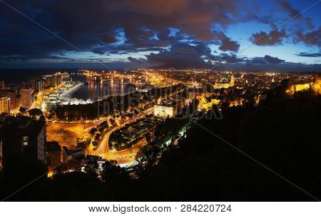 View of the Malaga city, Spain. Aerial view of City Hall and port with illuminated buildings at night with sunset sky