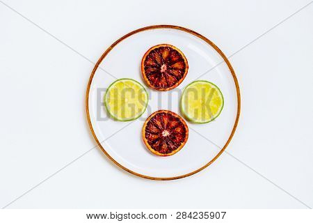 Lime and grapefruit on plate isolated on white background. Natural organic product. Symmetrical arrangement, flat lay styling. Top view. Creative still life idea of spring wallpaper. Art photography.