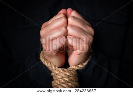 bound hands on a black background concept of slavery, human trafficking poster