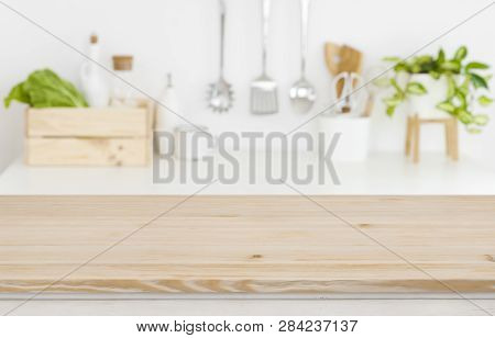 Blurred Kitchen Workplace With Empty Wooden Table Top In Front