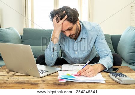 Angry Man Paying Bills As Home With Laptop And Calculator