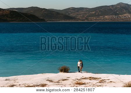 A Couple In Love Looks At The Blue Lagoon. Couple In Love On The Beach. Honeymoon Lovers. Man And Wo
