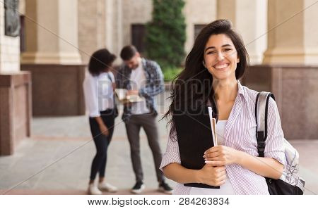 Happy Beautiful Student Girl With Backpack Holding Folders At University University And Friends Back