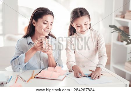 Contended Mother Enjoying Tea Break With Her Amusing Child