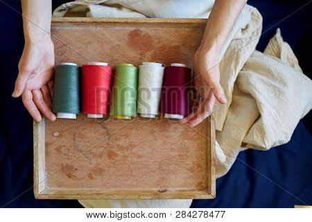 Seamstress or dressmaker keeps colorful spools of thread in hands on wooden background, top view. poster