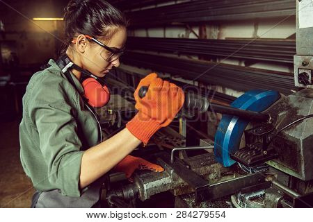 Busy and serious craftswoman grinding timbers with special machine. Beautiful woman wearing safety glasses. Concept of joiners shop and woodworking. Gender equality. Male profession poster