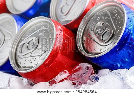 Soda Cans On Crushed Ice. Red And Blue Cans With Droplets Close-up Macro