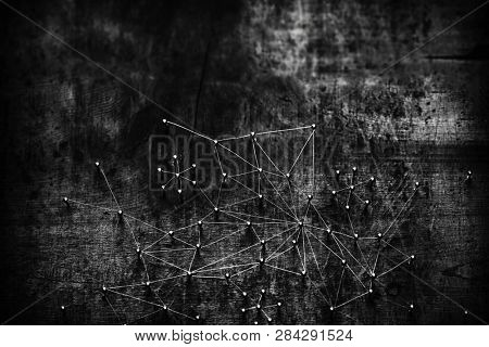 Linking entities. Network, networking, social media, internet communication abstract. Many small network connected to a larger network. Thin web of wires on rustic wood. Shallow Depth of field.