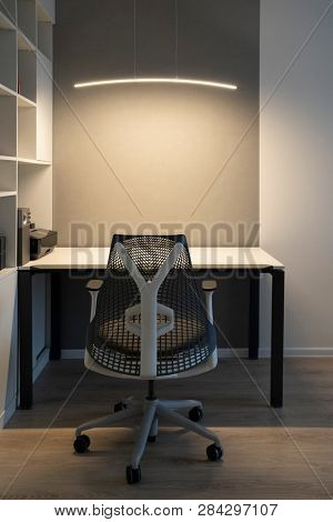 Well-organized ergonomics of workspace in the modern office. Computer table, orthopaedic chair and soft lighting above desk.