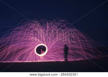 An image of a steel wool firework with shadow of a man