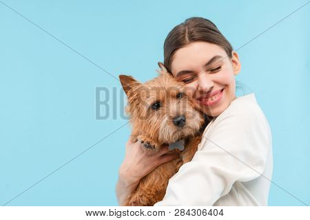 Cheerful young woman standing isolated over blue backgroundm hugging a dog