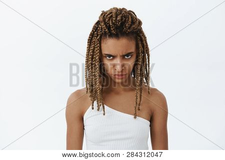 Waist-up Shot Og Angry And Moody Displeased Hateful Dark-skinned Young Female With Dreads Looking Fr