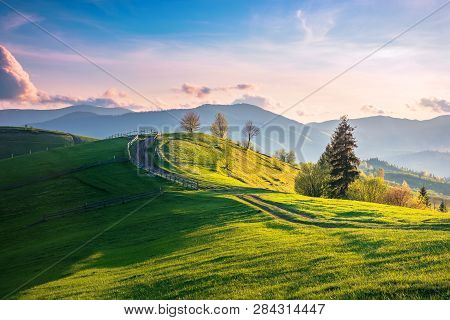 Beautiful Countryside In Mountains At Sunset. Country Road And Fence Through Field On Rolling Hill.