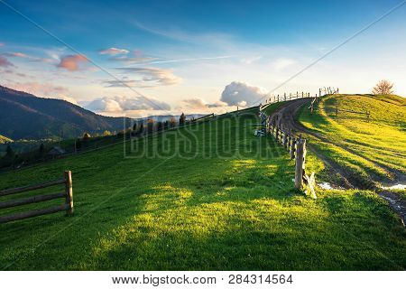 Beautiful Countryside Scenery In Mountains. Fence On The Grassy Field. Country Road Uphill The Knoll