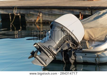 Detail Of One Outboard Motor (engine And Propeller), On A Boat Moored In The Port With Reflections