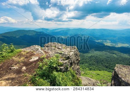 View From A Rocky Cliff In To The Distant Valley. Beautiful Summer Landscape In Mountains. Huge Ridg