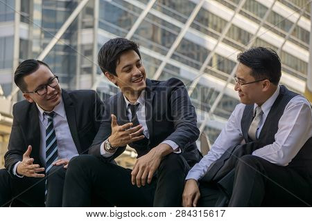 A Relaxed Conversation Of The Businessmans Outside The Office. Colleagues Enjoy Talking After Work.