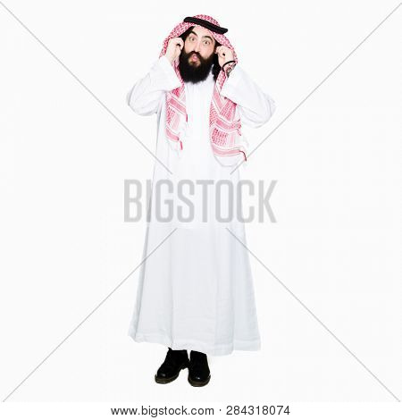 Arabian business man with long hair wearing traditional keffiyeh scarf Smiling pulling ears with fingers, funny gesture. Audition problem