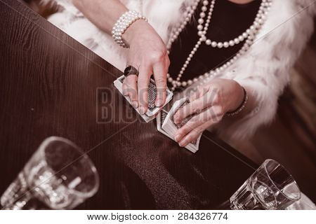 women's hands sharper prevents a deck of cards in an underground casino. close-up