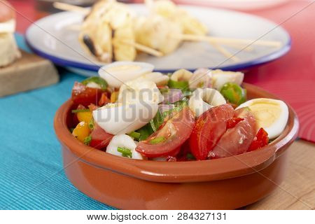Calamari Rings, Eggs And Tomatoes Salad In A Clay Bowl. Spanish Tapas Appetizers